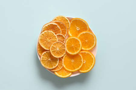 Sliced fresh and sliced fruits orange chips on blue background, home drying. Snack vegan free sugar food. View from above.