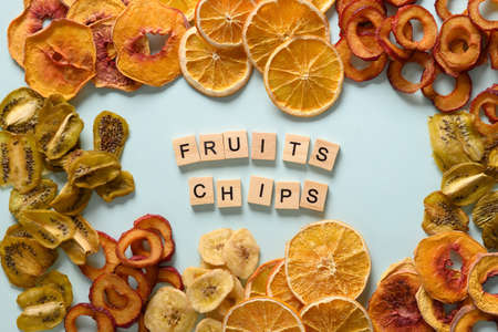 Dried sliced plums, kiwi, peach fruits chips on blue background and text - Fruits chips. Snack vegan free sugar food. View from above.