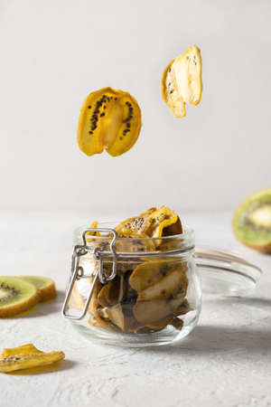 Kiwi chips glying to glass gar for storage and eating on light background, home drying. Vegan free sugar food. Close up. Vertical format.