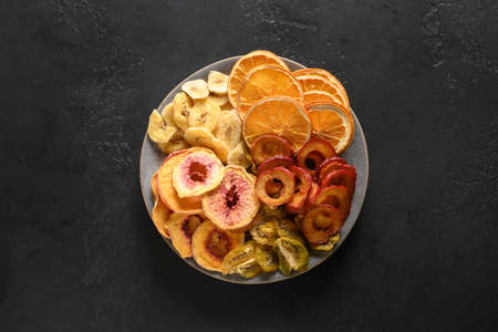 Dried sliced plums, kiwi, peach fruits chips on black. 版權商用圖片