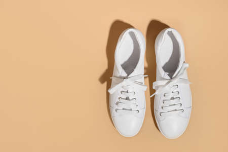 White female gumshoes on beige background. 版權商用圖片