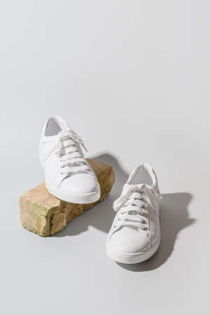 White womens new sneakers on natural stone as stand.