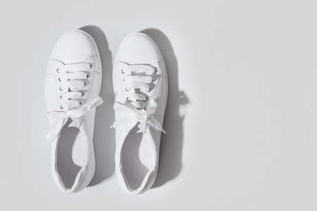 Pair of white female sneakers on yellow. Flat lay, top view minimal background. Magazine concept. 版權商用圖片