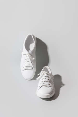 White womens new gumshoes or sneakers on grey.