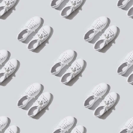 Seamless pattern of white female new gumshoes on grey background. Casual outfit.