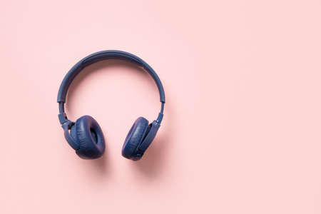 Blue wireless headphones on a pink background.