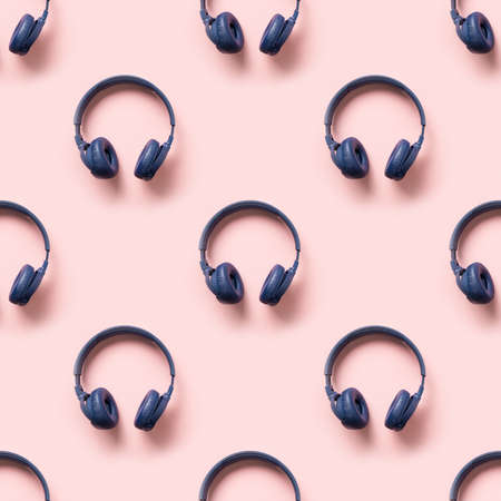 Seamless pattern of blue wireless headphones on pink background. 版權商用圖片