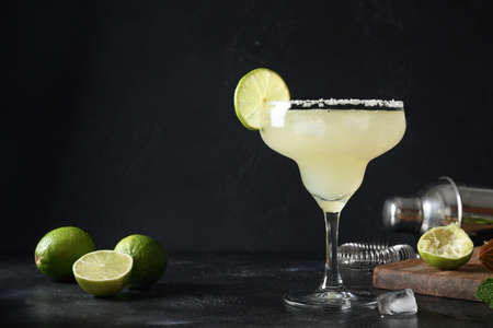 Classic Margarita cocktail with lime juice and ice cube on dark black background with copy space.
