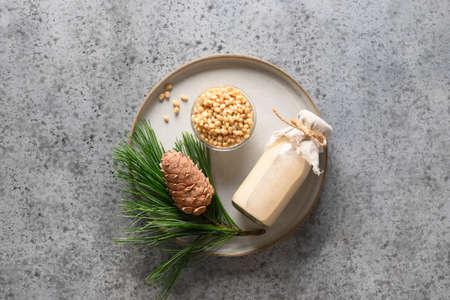 Vegan cedar nut milk in bottle on gray background. Non dairy alternative milk. Healthy vegetarian drink. Copy space