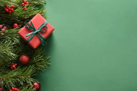 Christmas border with red gift and balls on green background.