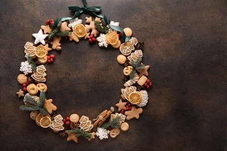 Creative sweet Christmas wreath of assorted cookies, berries on a brown background. Standard-Bild