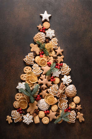 Creative Christmas tree of assorted cookies, cinnamon, anise stars, berries, orange chips, spruce branches.