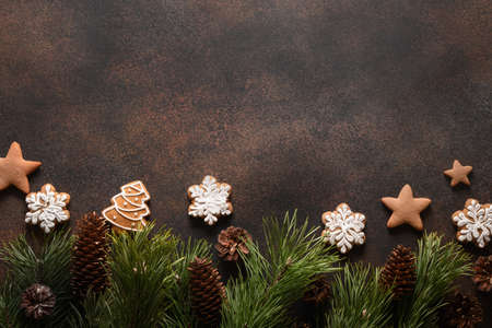 Christmas homemade assorted glazed cookies on brown background.