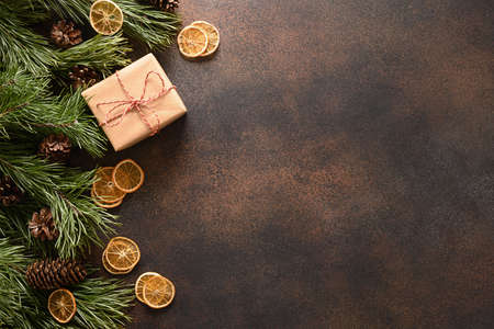 Christmas gift, aroma orange chips, fir tree and cones on brown background. Standard-Bild
