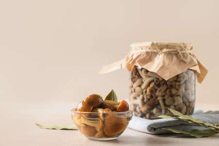 Pickled honey mushrooms served in bowl with bay leaf. Standard-Bild