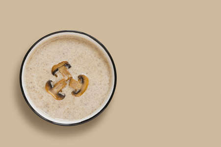 Mushroom champignon cream soup on beige background. View from above.