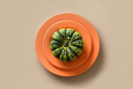 Autumn pumpkin in decorative orange plate, home decor concept. Standard-Bild