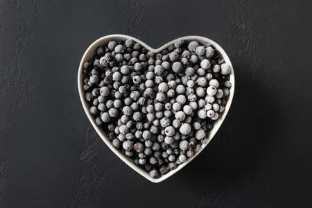 Frozen black currant in plate shaped as heart on a black background. View from above.