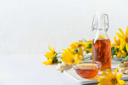 Jerusalem artichoke syrup in bottle, flowers and root.