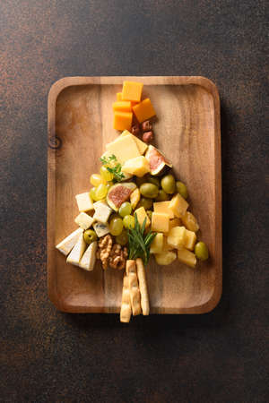 Cheese platter as Christmas tree with different cheese and appetizer.