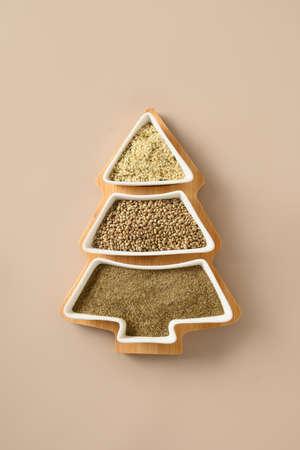 Hemp seeds, flour, kernels in plate shape of Christmas tree. Xmas vertical eco greeting card. Xmas tree.