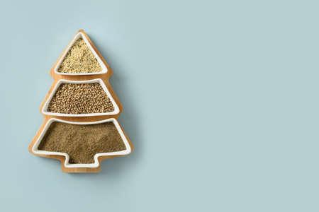 Hemp seeds, flour, kernels in plate shape of Christmas tree on blue background. Alternative Xmas eco greeting card.