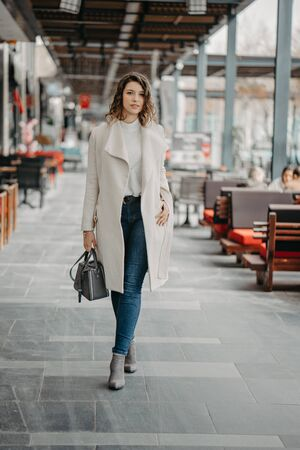 Beautiful young brunette girl walking on the restaurants street of the city