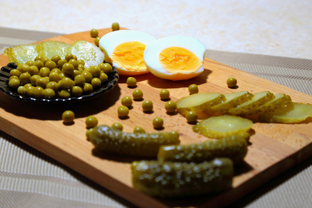 In the kitchen on the chopping board lie chicken eggs, canned green peas and pickled cucumbers.