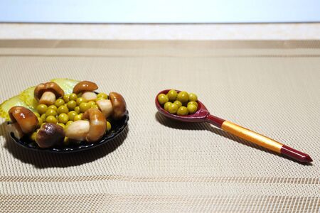 Snack assorted: canned green peas, pickled mushrooms and pickled cucumbers on a black plate with a wooden spoon.