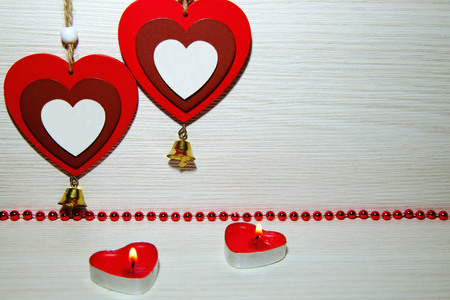 Two beautiful romantic hearts, burning candles and red beads. Symbol of love and St. Valentines Day. Stock Photo