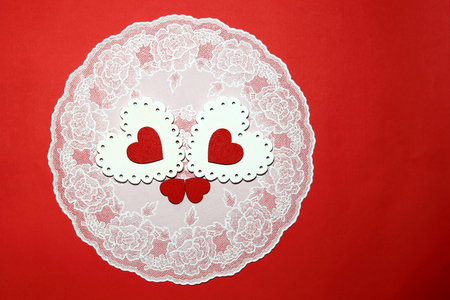 Valentines Day, wedding, love. White and red bright openwork wooden hearts on a lacy napkin on a red background with an empty space for writing congratulations or invitations.