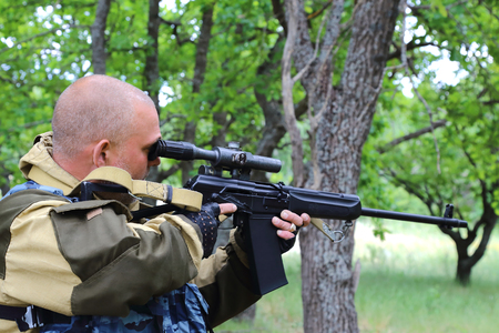 A man hunter is aiming from a gun in the forest. Sighting the gun barrel at the target.
