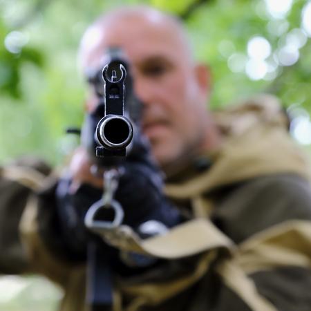 The man hunter is aiming at the gun. Sighting the gun barrel at the target.