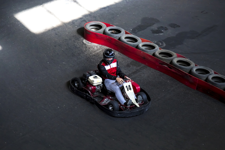 Riding on karting on the auto track. The young guy drives karting.