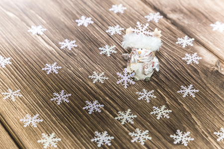 Christmas and New Year festive background. A smiling snowman and a lot of snowflakes on a wood texture background. Stock Photo