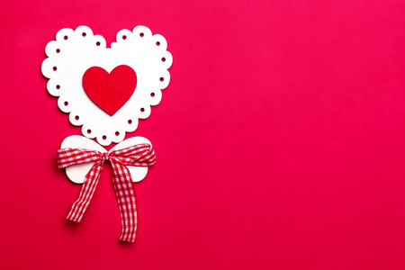Valentine's day holiday, mother's day, March 8, wedding invitation. Symbol of love white wooden heart on a red background with empty space for text Banco de Imagens