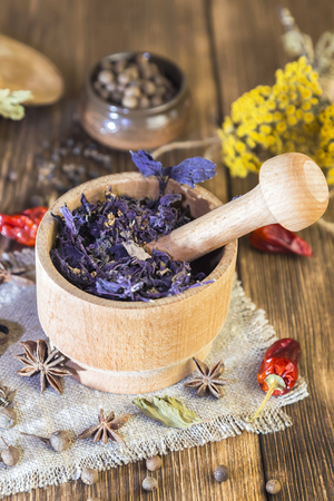 Fragrant dried healing herbs for therapy and spicy spices. On the table in a mortar are purple basil, tansy, pepper, chili and cardamom, in a rustic style. 免版税图像