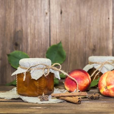 Essen, Ernte, Obstkonserven. Würzige Pfirsichmarmelade in einem Glas mit frischem reifen Früchten Zimt auf Holzhintergrund im rustikalen Stil Standard-Bild