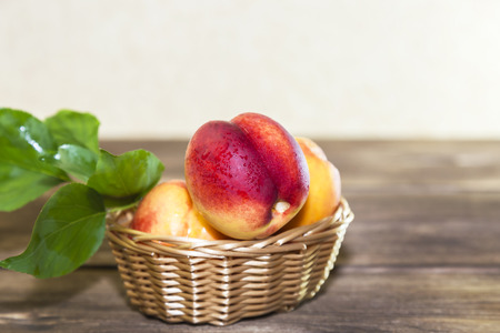 Food, harvest, fresh fruit. Ripe fruit of juicy peach with water drops and leaves in a wicker basket on a wooden background in a rustic style with a copy space