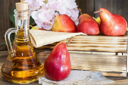 Jedzenie, wegetarianizm, zdrowa dieta jedzenie, picie. Naturalny sok bez miąższu ze świeżej czerwonej gruszki w szklanej karafce, wino, likier i sezonowy zbiór owoców w drewnianym pudełku na stole