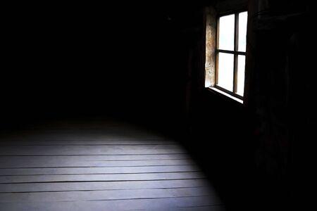 Dunkelheit und Horror, Hintergrund mit Kopienraum. Drinnen in einem leeren dunklen Raum eines alten verlassenen Hauses mit schwarzen Wänden mystisches Licht in der Dunkelheit des Fensters mit einem Fleck auf dem Boden Standard-Bild