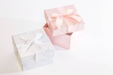 Two decorative holiday gift boxes with ribbon bow for congratulations, surprise, presentation in white and pink on a white background Stock Photo