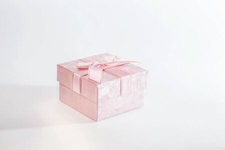 One decorative holiday gift box with ribbon bow for congratulations, surprise, pink present on white background with copy space Stock Photo