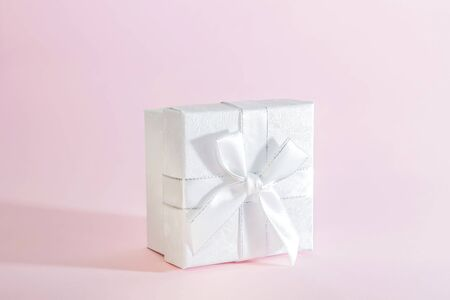 One decorative holiday gift box with a ribbon bow for congratulations, surprise, presentation, white silver on a delicate pink background in pastel colors with a copy space Stock Photo