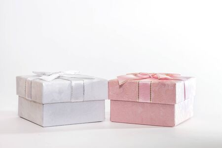 Two decorative holiday gift boxes with ribbon bow for congratulations, surprise, white and pink presentations on a white background with copy space