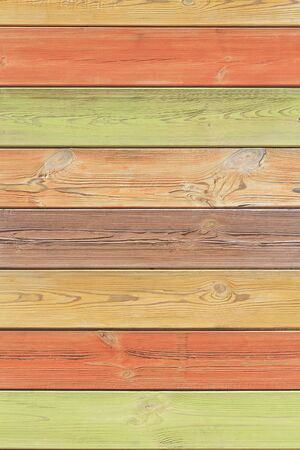 Abstract multicolored colorful vertical striped background in beautiful pastel autumn colors with the surface texture of wooden boards painted in yellow orange green brown colors