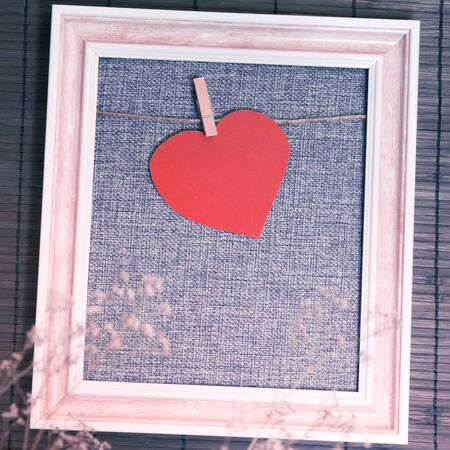 Original photo frame blank with hearts for congratulations on Valentine's Day in gray, pink in brown tones for home decor with natural dry flowers with rough texture with copy space