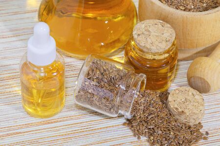 Vegetarian diet healthy vitamin food, cosmetology, traditional alternative medicine, seasoning natural vegetable linseed oil in a bottle and flax seeds in a glass jar and a wooden mortar on the table