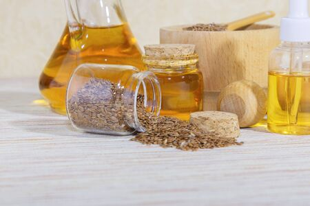 Vegetarian diet healthy vitamin food, cosmetology, personal care, self-eare, traditional alternative medicine, seasoning natural vegetable linseed oil in a bottle and flax seeds in a glass jar and wooden mortar