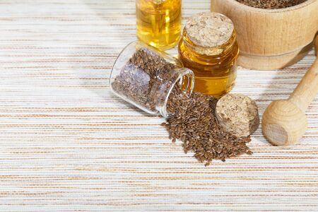 Vegetarian diet healthy vitamin food, cosmetology, personal care, self-eare, traditional alternative medicine, natural vegetable linseed oil in a bottle, flax seeds in a wooden mortar on a table with copy space